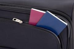 Zwarte reiskoffer en twee paspoorten Royalty-vrije Stock Afbeeldingen