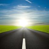 Zwarte rijweg tegen een verbazende zonsopgang royalty-vrije stock afbeeldingen