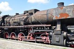 Zwarte roestige uitstekende stoomtrein op een platform stock afbeeldingen