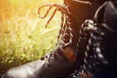 Zwarte ruwe laarzen met een hoge hoogste tribune in het gras in de zomer stock afbeelding