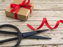 Zwarte schaar, gouden gift en lint op houten achtergrond Stock Fotografie