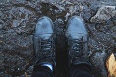 Zwarte schoenen in de modder Mening van hierboven royalty-vrije stock afbeeldingen
