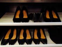 Zwarte schoenen in kast, één tot één, het suèdeschoenen van mooie vrouwen met een lage stabiele hiel stock afbeelding