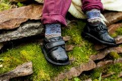 Zwarte schoenen met gekleurde sokken op kindbenen royalty-vrije stock afbeeldingen