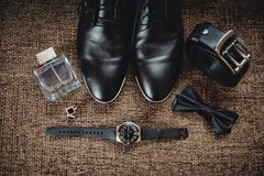 Zwarte schoenen, zwart band, zwart horloge, zwarte vlinder, cufflinks en parfum op een bruine achtergrond met het ontslaan royalty-vrije stock fotografie