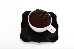 Zwarte schotel en kop met koffiebonen en grondkoffie Stock Afbeeldingen