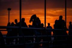 Zwarte silhouetten van mensen op de waterkant in het oranje licht van zonsondergang stock afbeelding