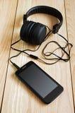 Zwarte smartphone en hoofdtelefoons Stock Foto's