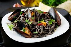 Zwarte Spaghetti Zwarte zeevruchtendeegwaren met mosselen over zwarte achtergrond stock foto's