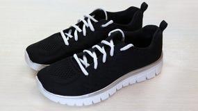 Zwarte sport unisex-tennisschoenen met wit enig en wit kant op witte achtergrond stock fotografie