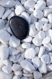 Zwarte steen op kiezelstenen Royalty-vrije Stock Fotografie