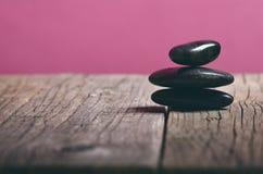 Zwarte steenbehandeling op een houten lijst Kuuroord en wellnessconcept Stock Afbeeldingen