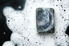 Zwarte steenkoolstuk zeep in schuim op dark stock afbeelding