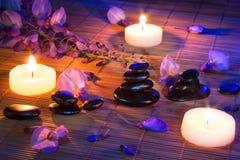 Zwarte stenen, violette bloemen, en kaarsen op bamboe Stock Foto