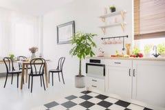 Zwarte stoelen bij eettafel met bloemen in wit vlak binnenland met installatie naast kitchenette Echte foto stock afbeeldingen