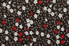 Zwarte stof als achtergrond met rode en witte bloemen stock afbeeldingen