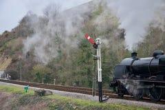 Zwarte stoomtrein op spoorlijnspoor onder heuvel dichtbij signaalpost stock afbeeldingen