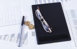 Zwarte tabletruchkaa en glazen die op de financiële tabellen en de grafieken liggen stock fotografie