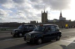 Zwarte taxicabines Londen Stock Afbeeldingen
