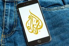 Zwarte telefoon met embleem van nieuwsmedia Al Jazeera op het scherm stock foto's