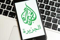 Zwarte telefoon met embleem van nieuwsmedia Al Jazeera op het scherm stock afbeelding
