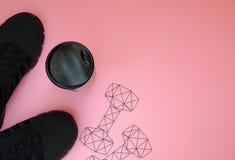 Zwarte tennisschoenen; bottel en de veelhoekige gewichten van de gymnastiekdomoor royalty-vrije stock foto's