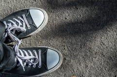 Zwarte tennisschoenen op een achtergrond van asfaltweg stock foto