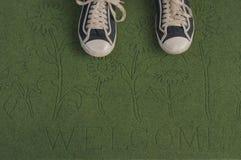 Zwarte tennisschoenen op een groene welkome mat Royalty-vrije Stock Afbeeldingen