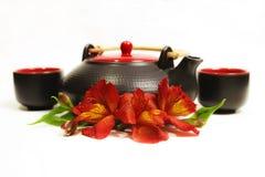 Zwarte thee en koppen met bloemen Stock Foto's