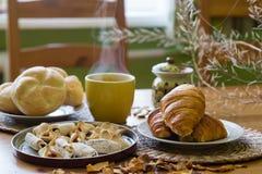 Zwarte thee in gele mok met croissants, broodjes en eigengemaakte koekjes royalty-vrije stock fotografie