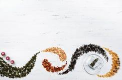Zwarte thee, groene thee, fruitthee, bruine suiker op houten witte achtergrond royalty-vrije stock foto