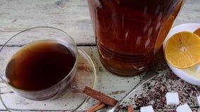 Zwarte thee, handpers met citroenen Een kruik zwarte thee en kubussen van suiker stock footage