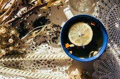 Zwarte thee met blauwe bloemen, sinaasappelschil en bloemblaadjes in blauw en royalty-vrije stock afbeeldingen
