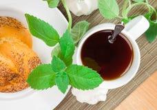 Zwarte thee met broodje Stock Fotografie