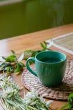 Zwarte thee met citroen in groene mok met sneeuwklokjesachtergrond Stock Foto