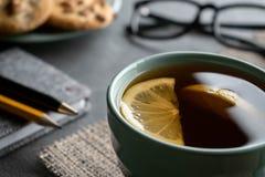Zwarte thee met citroenplakken op een servet van jute met blocnotepen, een potlood een plaat van koekjes en glazen stock afbeelding