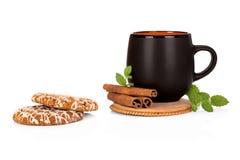 Zwarte theekop met kaneel en koekjes op wit Royalty-vrije Stock Afbeelding