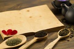 Zwarte theepot, koppen, theeinzameling, bloemen, oud leeg open boek op houten achtergrond Menu, recept Stock Afbeelding