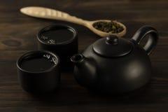 Zwarte theepot, twee koppen op oude houten achtergrond menu Stock Foto
