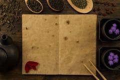 Zwarte theepot, twee koppen, theeinzameling, bloemen, oud leeg open boek op houten achtergrond Menu, recept Royalty-vrije Stock Afbeeldingen