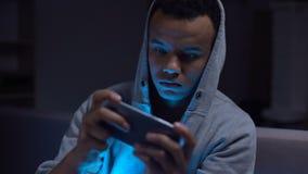 Zwarte tiener het spelen videospelletjes op telefoon, kwaad voor geestelijke gezondheid en zicht stock video