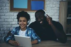 Zwarte tienerjongen die in hoofdtelefoons aan muziek luisteren stock foto