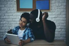 Zwarte tienerjongen die in hoofdtelefoons aan muziek luisteren stock fotografie