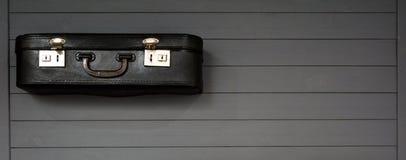 Zwarte uitstekende koffers op de houten grijze achtergrond Stock Foto