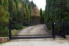 Zwarte vervaardigde poort aan bezit met tuin op de achtergrond royalty-vrije stock foto