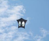 Zwarte vlieger met ogen tegen de blauwe hemel Stock Afbeeldingen