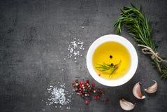Zwarte voedselachtergrond met olijfolie en kruiden Stock Afbeeldingen