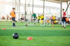 Zwarte voetbal op groen kunstmatig gras met het voetbalteam van de tellerskegel onscherpe opleiding royalty-vrije stock afbeelding