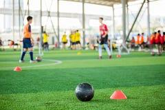 Zwarte voetbal op groen kunstmatig gras met het voetbalteam van de tellerskegel onscherpe opleiding stock afbeelding
