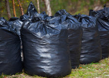 Zwarte, volledige en gebonden vuilniszakken die zich op de straat verenigen, in openlucht royalty-vrije stock fotografie